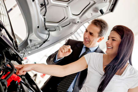 Woman at the dealer looking at a car engine  photo