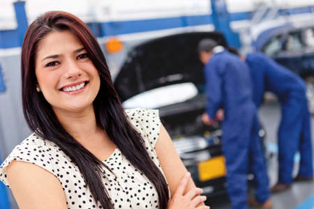 car garage: Woman at a car garage getting mechanical service