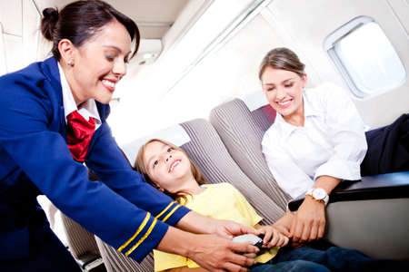 air hostess: Flight attendant fastening seat belt to boy for a safe trip