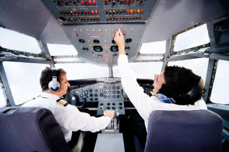 aviators: Pilots inside a cabin flying an airplane Stock Photo
