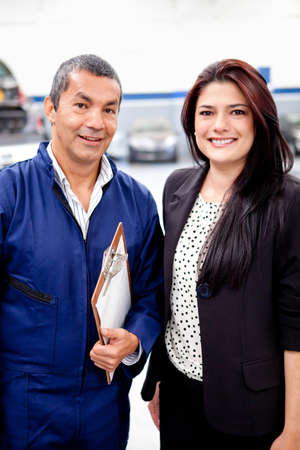 auto repair shop: Woman with the mechanic at a car garage