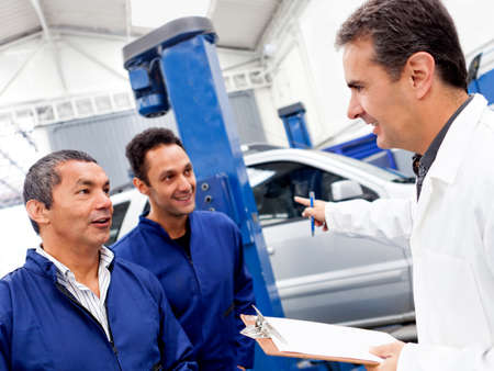 car garage: Group of mechanics talking at a car garage