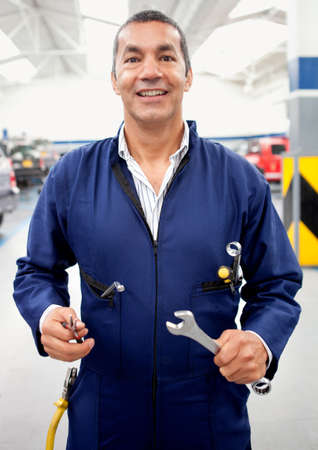 car garage: Male mechanic holding tools at a car garage and smiling
