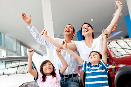 Excited family buying a car and celebrating with arms up  photo