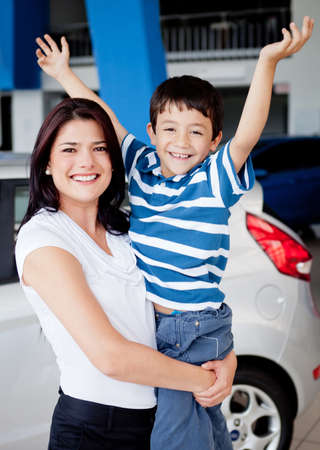 automobile dealership: Happy mother and son buying a car