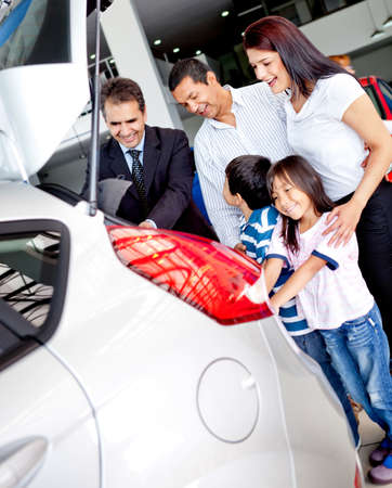 people buying: Family at the dealer buying a new car