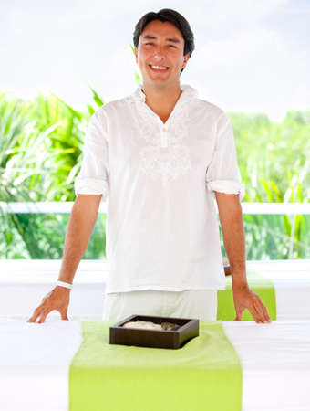 Friendly male masseur at an outdoors spa smiling photo