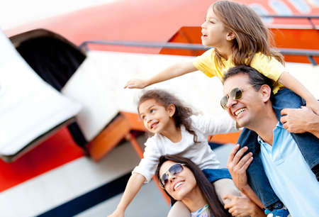 family vacation: Excited family with arms up traveling by airplane Stock Photo
