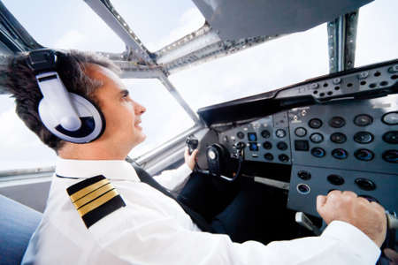 Male pilot sitting in the cabin and flying an airplane  photo