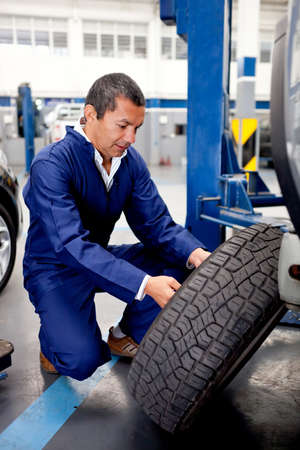tire: Mechanic fixing car wheel after a puncture