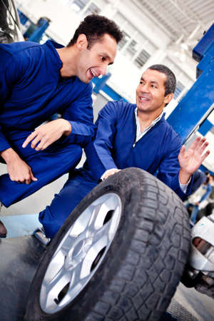 puncture: Male mechanics working as a team on car puncture