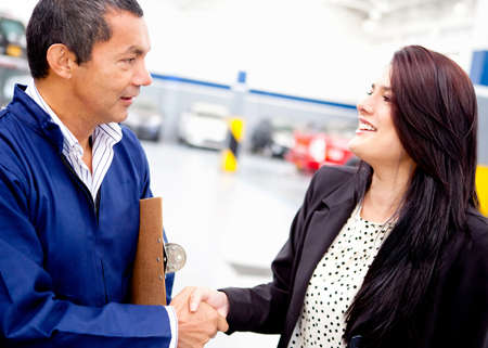 good service: Woman at the mechanic handshaking after a good service  Stock Photo