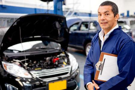 auto monteur: Man monteur bij een garage doen checkup Stockfoto