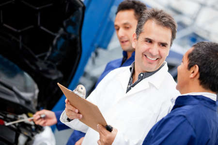 Group of male mechanics working at a car garage  photo
