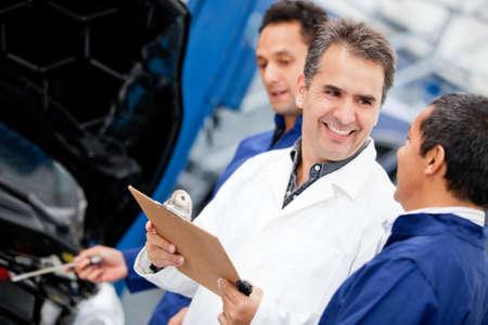 supervisores: Grupo de hombres de la mec�nica de trabajo en un garaje