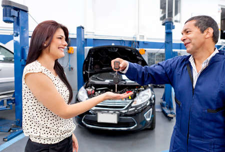 auto garage: Woman getting back her car from the mechanic after a checkup