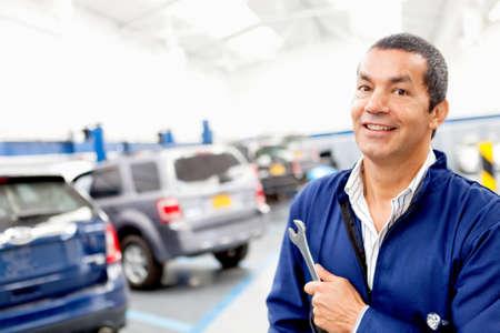 mecanico: Hombre mec�nico que trabaja en un taller de reparaci�n y la celebraci�n de las herramientas Foto de archivo