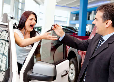 Happy woman buying a new car and salesman handling keys photo