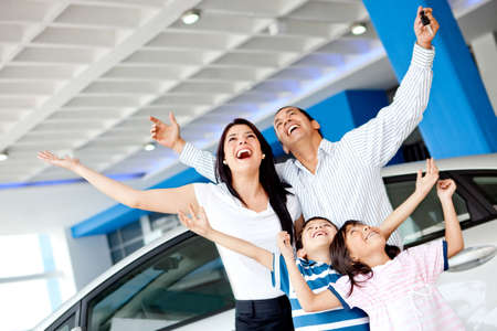 Excited family at the dealer buying a car and celebrating  photo