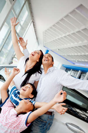 Family celebrating buying a new car with arms up  photo