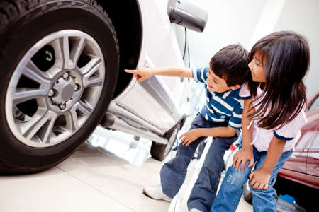 llantas: Los ni�os en el concesionario mirando las ruedas de coche Foto de archivo