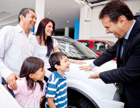 vendedores: Familia feliz con el concesionario la compra de un coche nuevo Foto de archivo