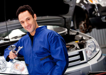 car garage: Male mechanic at a car garage smiling and holding tools