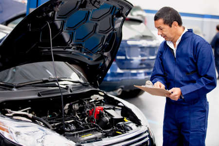 engineering clipboard: Mechachic checking on a car engine and taking notes  Stock Photo