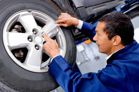 Male mechanic at a car garage fixing a wheel photo