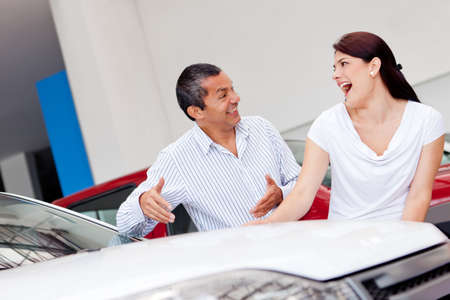 Happy couple looking for a new car at the dealer  photo
