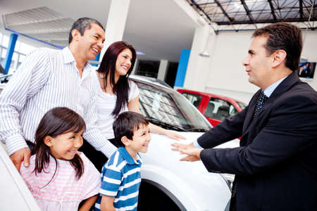 Family with a car salesman at the dealer  photo