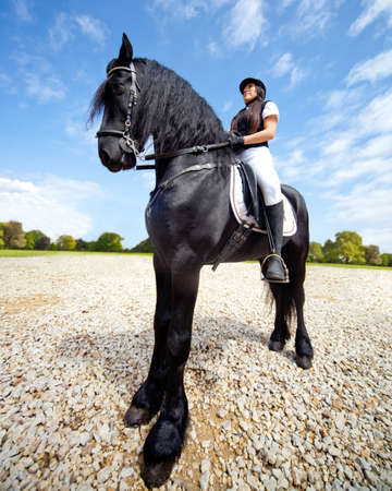 Female jockey riding a beautiful black horse  photo