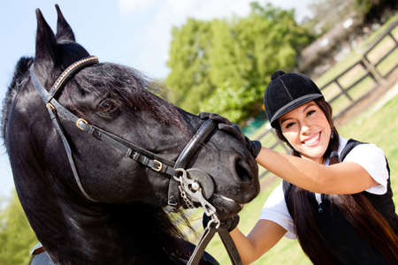 Portrait of a female jockey with a horse outdoors  photo