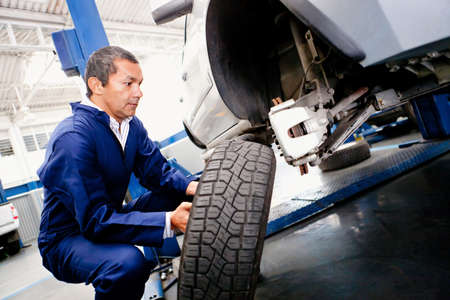repair shop: Mechanic placing a wheel back into a car Stock Photo