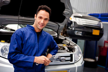 car garage: Male mechanic at a car garage holding tools and smiling  Stock Photo