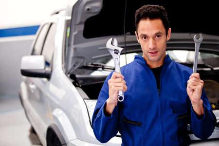 Car mechanic holding tools at the garage  photo