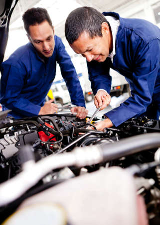 auto garage: Car mechanics working on a broken engine  Stock Photo