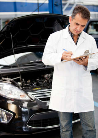car repair shop: Male mechanic taking notes at a car repair shop Stock Photo