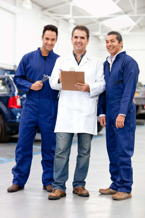 mechanic: Group of male mechanics smiling at a car repair shop Stock Photo
