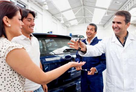 fixed: Joven de tomar coche al taller de reparaciones que se fijar� Foto de archivo