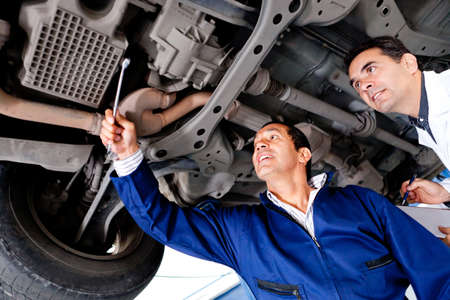 Group of mechanics fixing a car at the garage  Stock Photo - 12824605