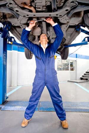 Mec�nico trabajando sobre un chasis de coches en el garaje photo