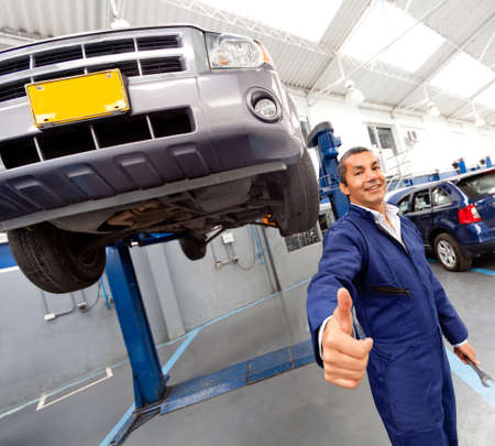 Happy mechanic at a car garage with thumbs up  photo