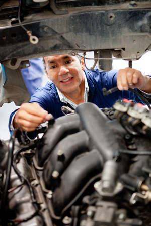 Male mechanic fixing a broken car at the repair shop  photo