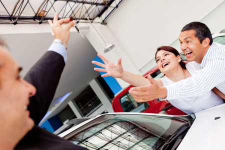 Excited couple buying a car and reaching for the keys  Stock Photo - 12824652