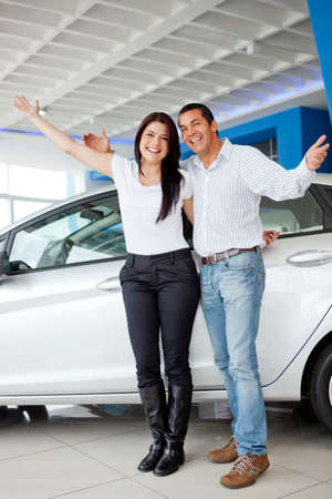 Happy couple with new car at the dealership  photo