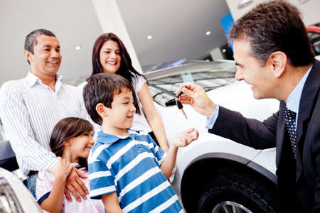 Family buying a new car and getting the keys from salesman photo
