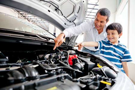 Father teaching car mechanics to his son and pointing the engine  photo