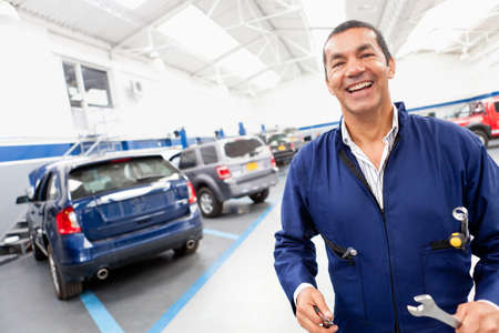 Friendly mechanic at a car garage smiling  photo