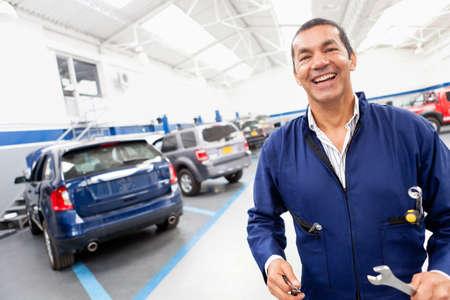 car repair shop: Friendly mechanic at a car garage smiling